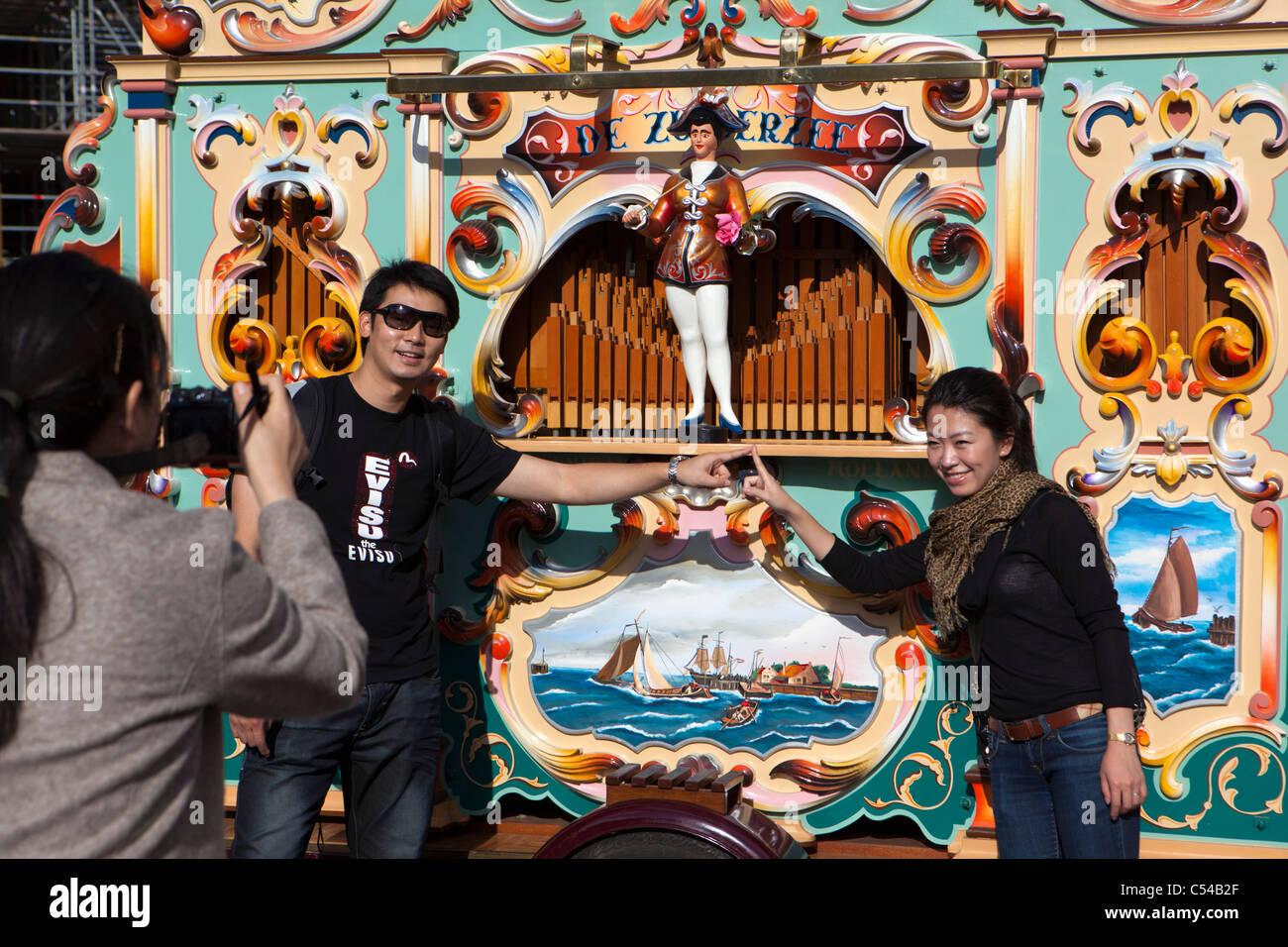 I Paesi Bassi, Amsterdam, parata annuale degli organi di strada su Piazza Dam. Turisti asiatici, uomo e donna, aventi Immagini Stock