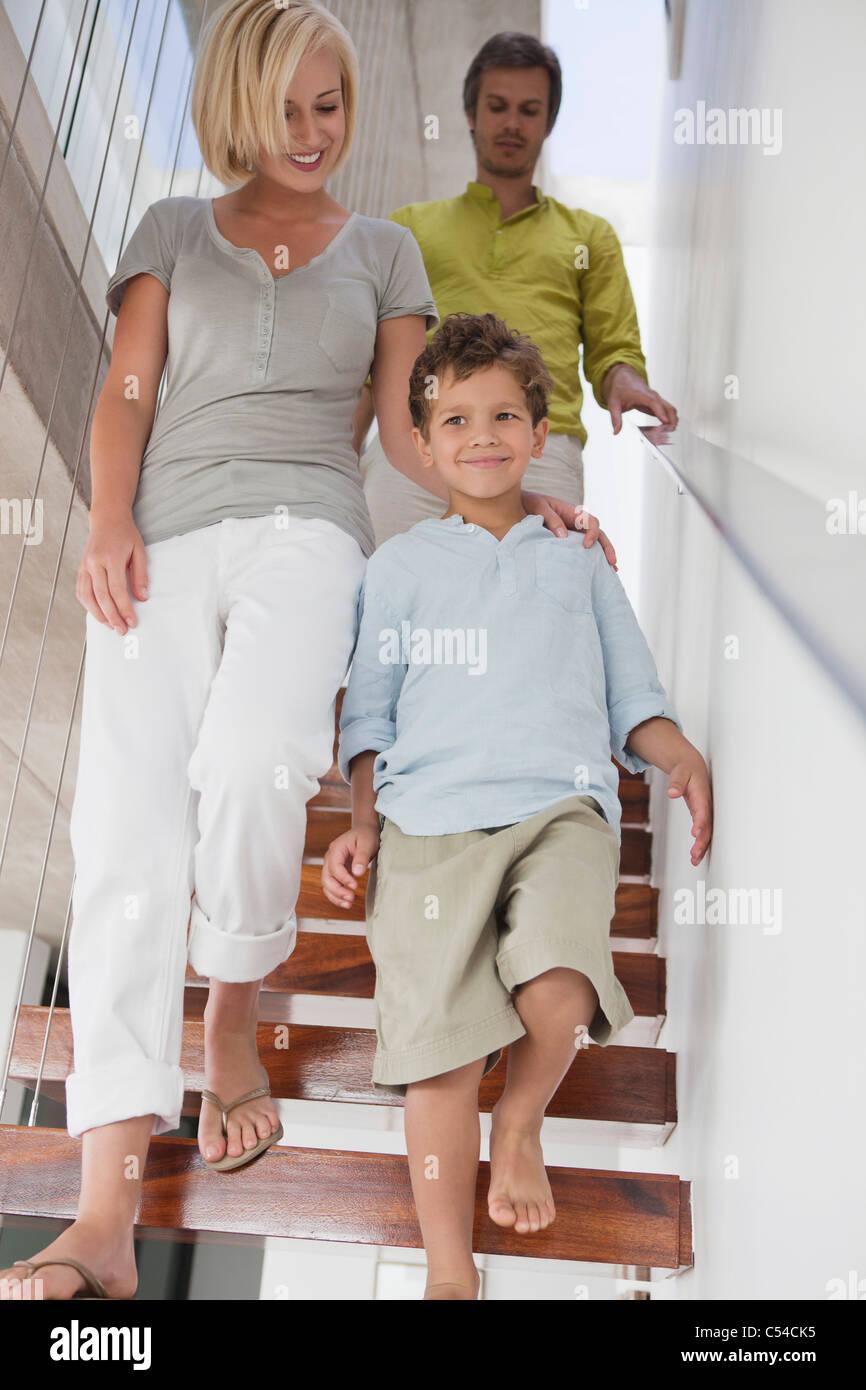 Coppia con il loro figlio si sta spostando verso il basso da una scala Immagini Stock