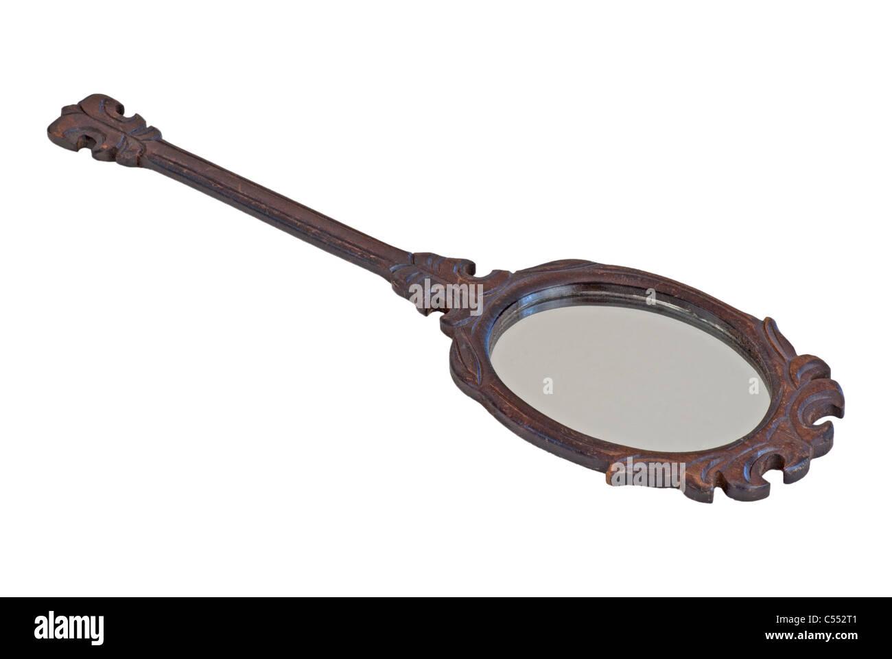 Vintage specchio a mano con legno intagliato trim. Immagini Stock