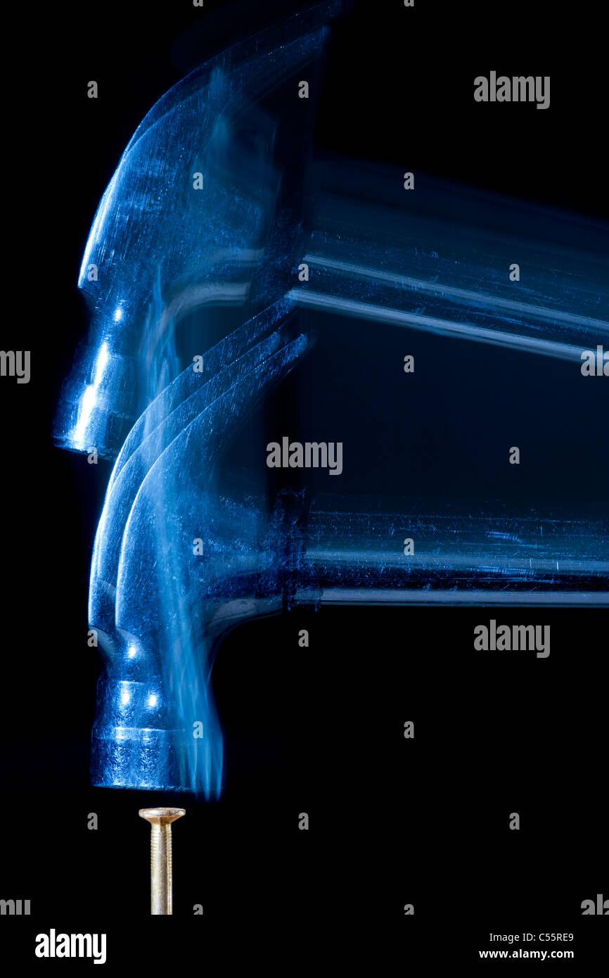 Slow motion vista stroboscopico di falegname martello colpisce le unghie. Immagini Stock