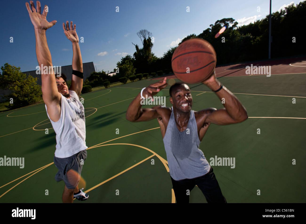 I maschi a giocare all'aperto gioco di basket Immagini Stock