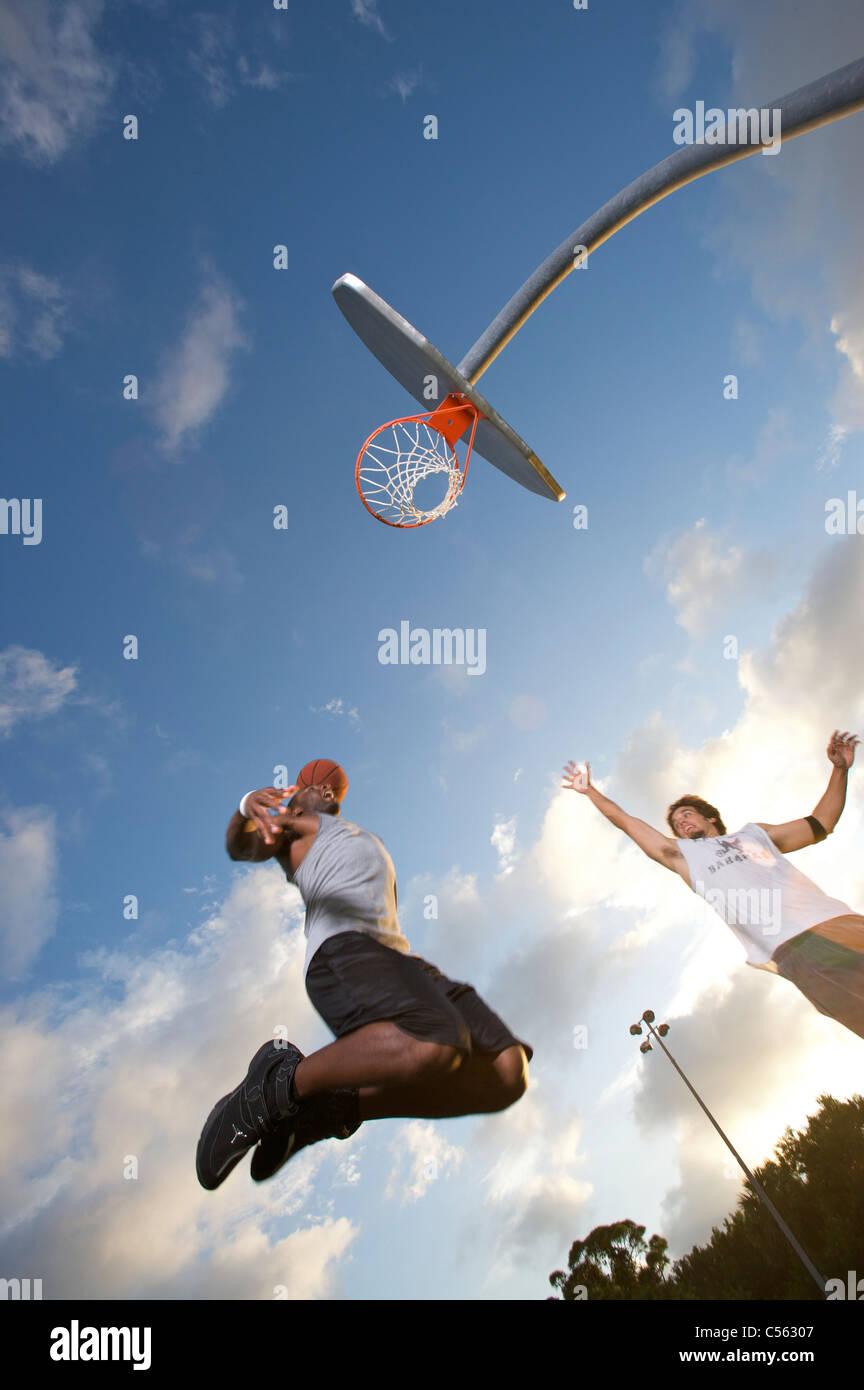 Punteggio maschio all'aperto durante il gioco del basket, inclinazione verso l'alto verso il traguardo Immagini Stock