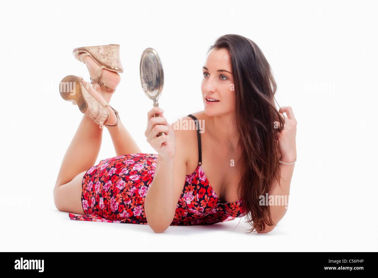 Donna in abiti estivi guardando lo specchio a mano - isolato su bianco Immagini Stock