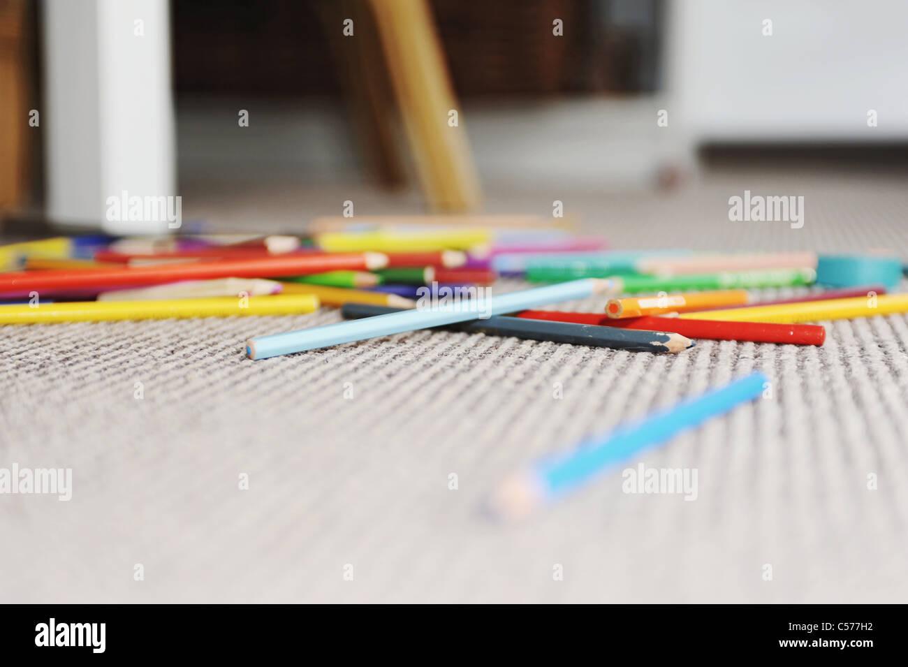 Matite colorate in pila sul pavimento Immagini Stock