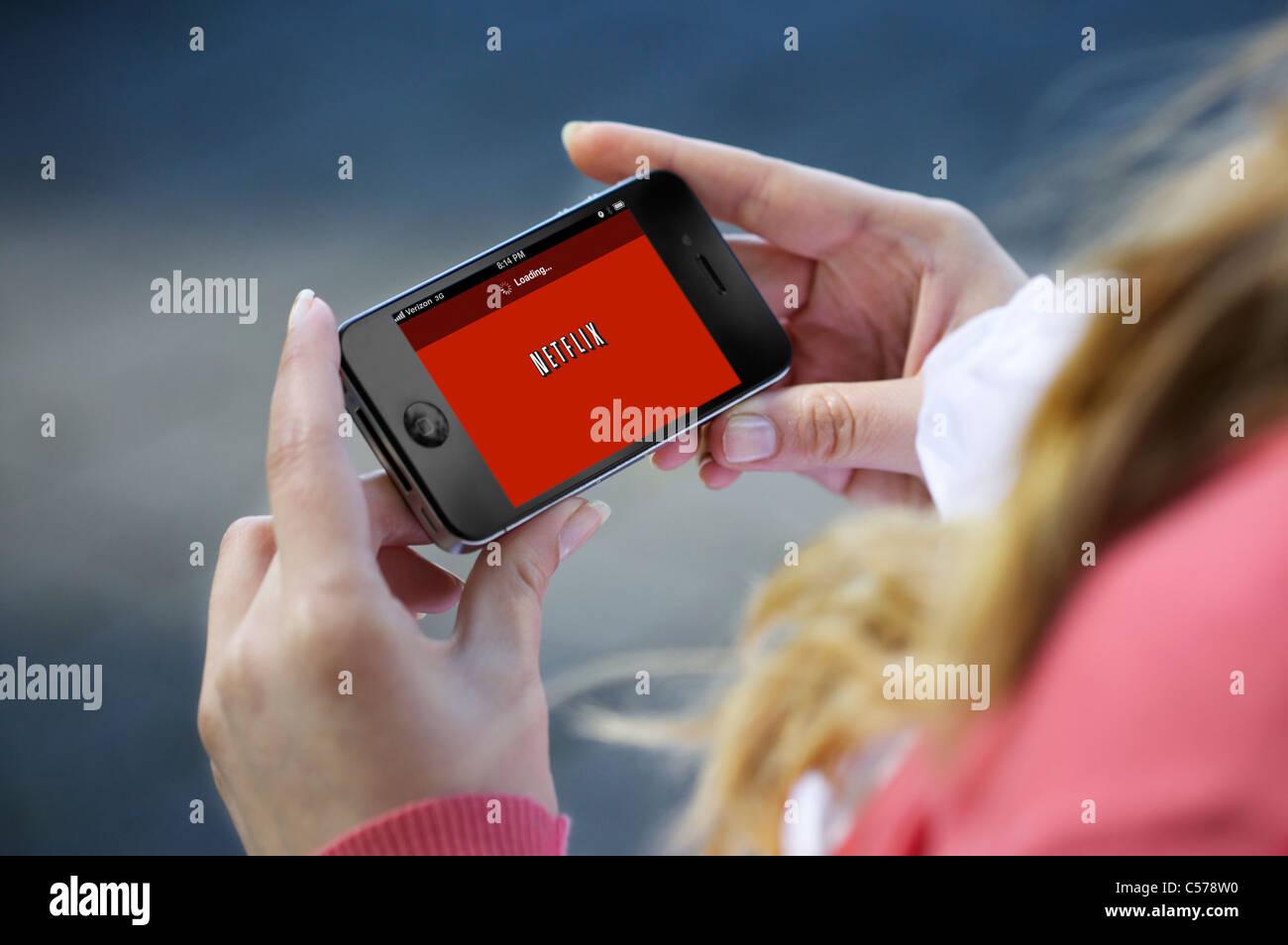 Chiudere l immagine di una donna guardare film su Netflix (film online noleggio) app da un iPhone 4 Immagini Stock