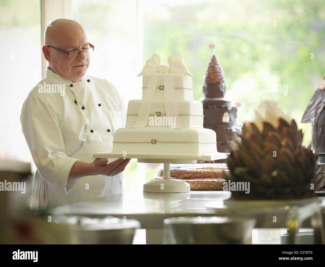 Baker controllo decorativo torta di nozze Immagini Stock