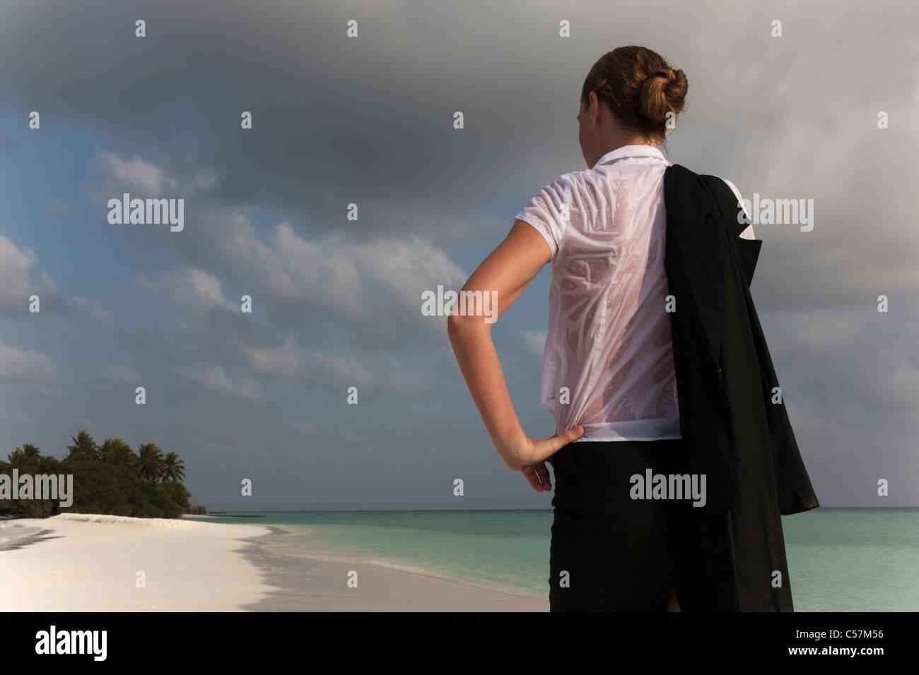 Donna che indossa vestiti bagnati sulla spiaggia Immagini Stock