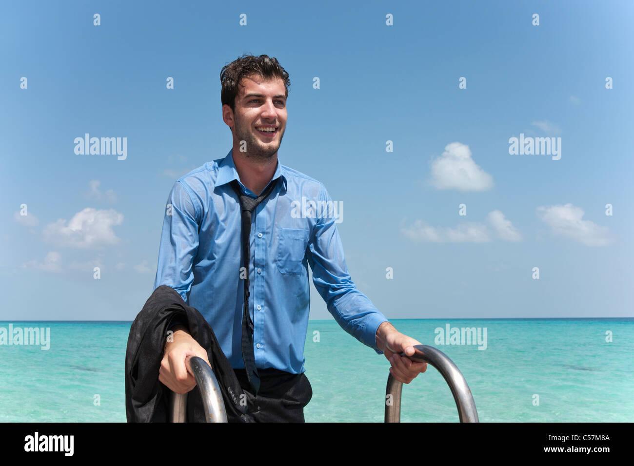 Imprenditore in vestiti bagnati dock di arrampicata Immagini Stock