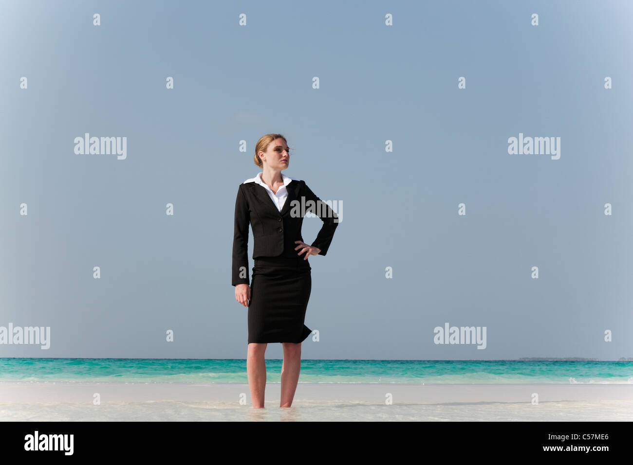 Imprenditrice permanente sulla spiaggia tropicale Immagini Stock
