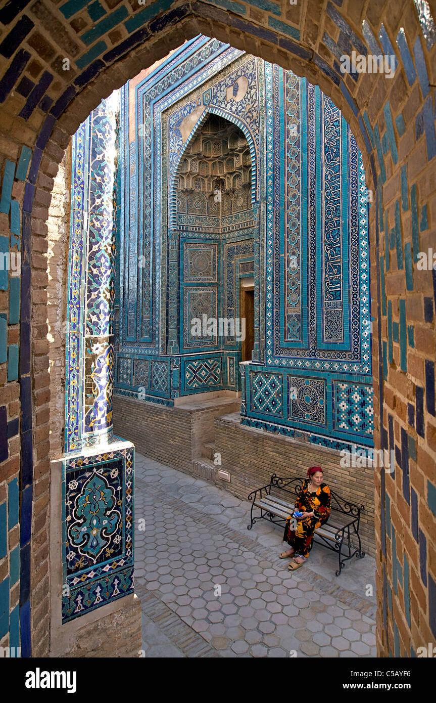 Uzbeko donna seduta sul banco a Shahr mi Zindah, Samarcanda, Uzbekistan Immagini Stock