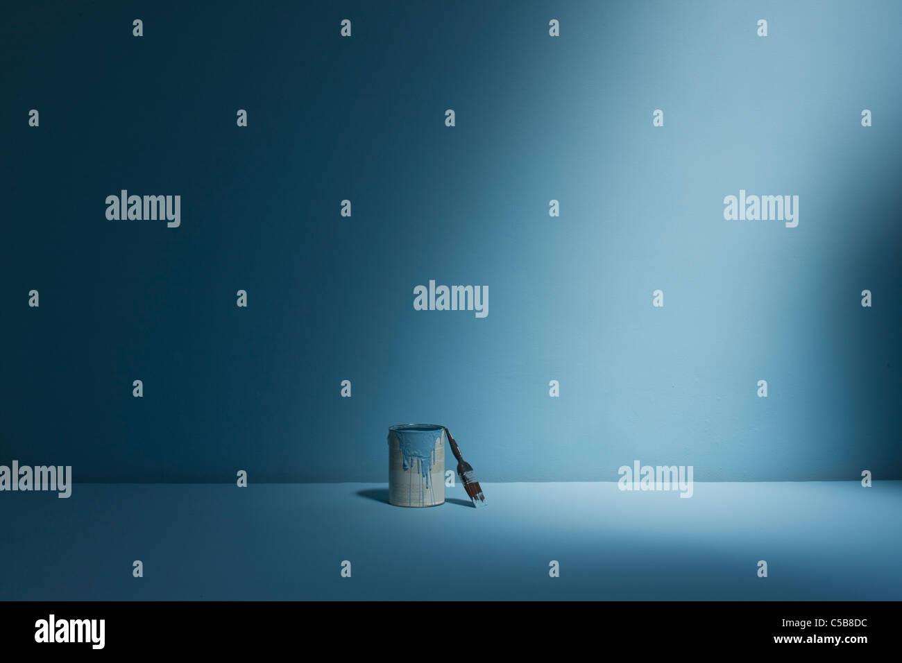 Vaso di vernice e il pennello su sfondo blu Immagini Stock