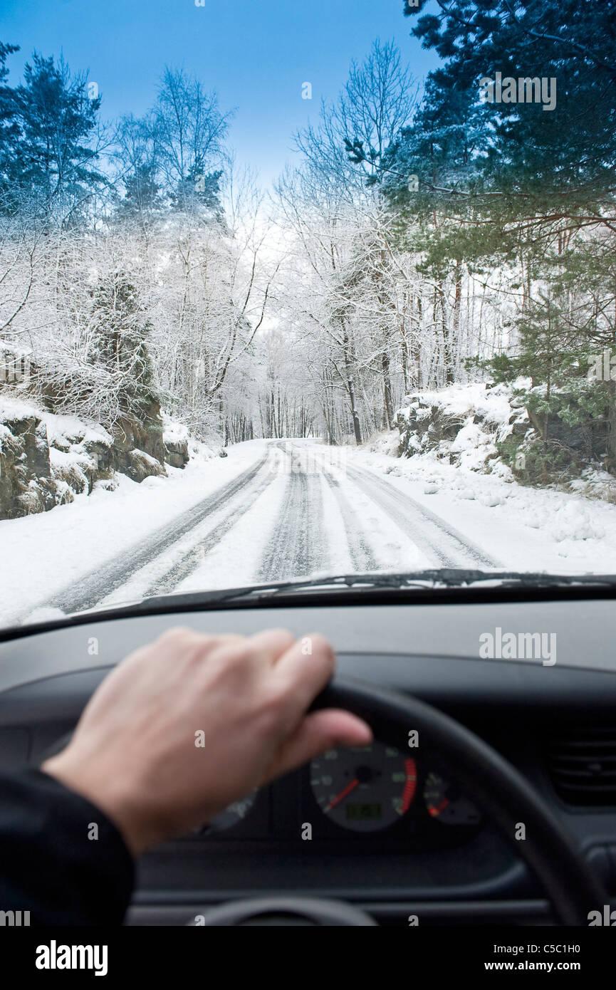 Le mani sul volante di sterzo con la vista della strada innevata e alberi avanti Immagini Stock