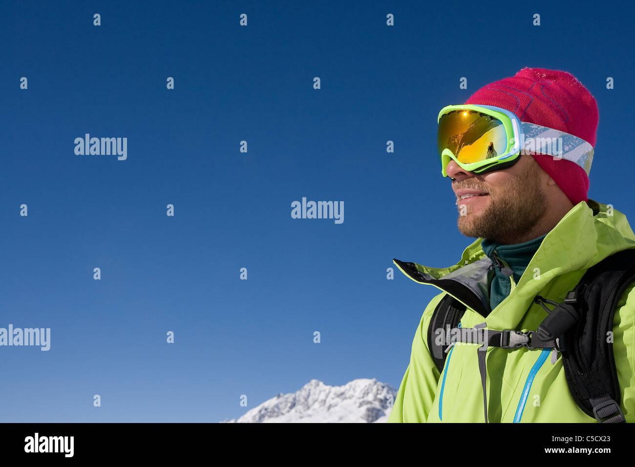 Vista laterale di un maschio di sciatore in maschere da sci contro il cielo blu chiaro Immagini Stock