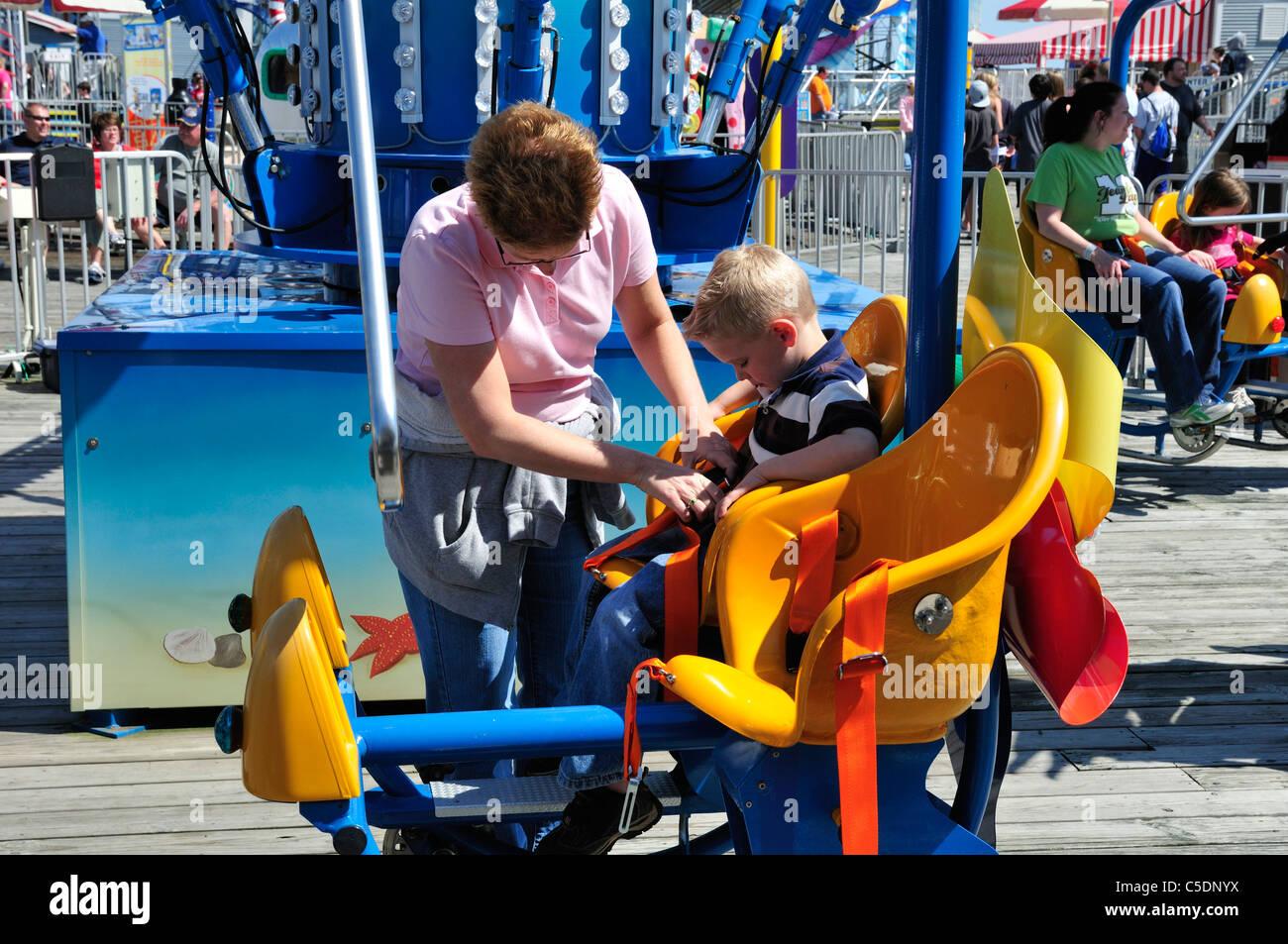 Una donna si aggancia un ragazzo del cablaggio di sicurezza su un divertimento ride in Wildwood, New Jersey Foto Stock