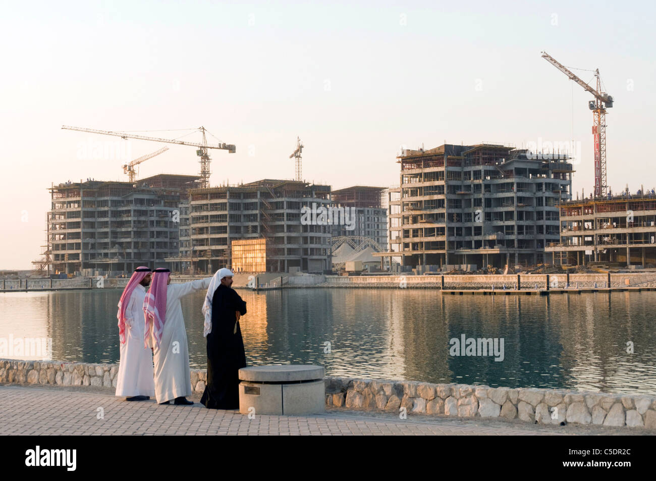 Elk204-1007 Bahrain, Manama, arabo di uomini in abito tradizionale guardando in alto della costruzione di tutta Immagini Stock