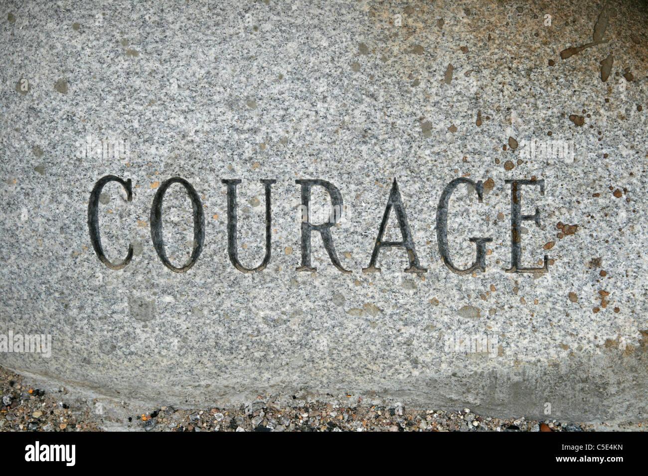 La parola coraggio scolpito su un granito pietra ciottoli Immagini Stock