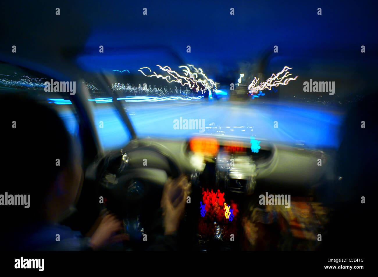 Close-up vista offuscata delle mani sul volante in un auto Immagini Stock
