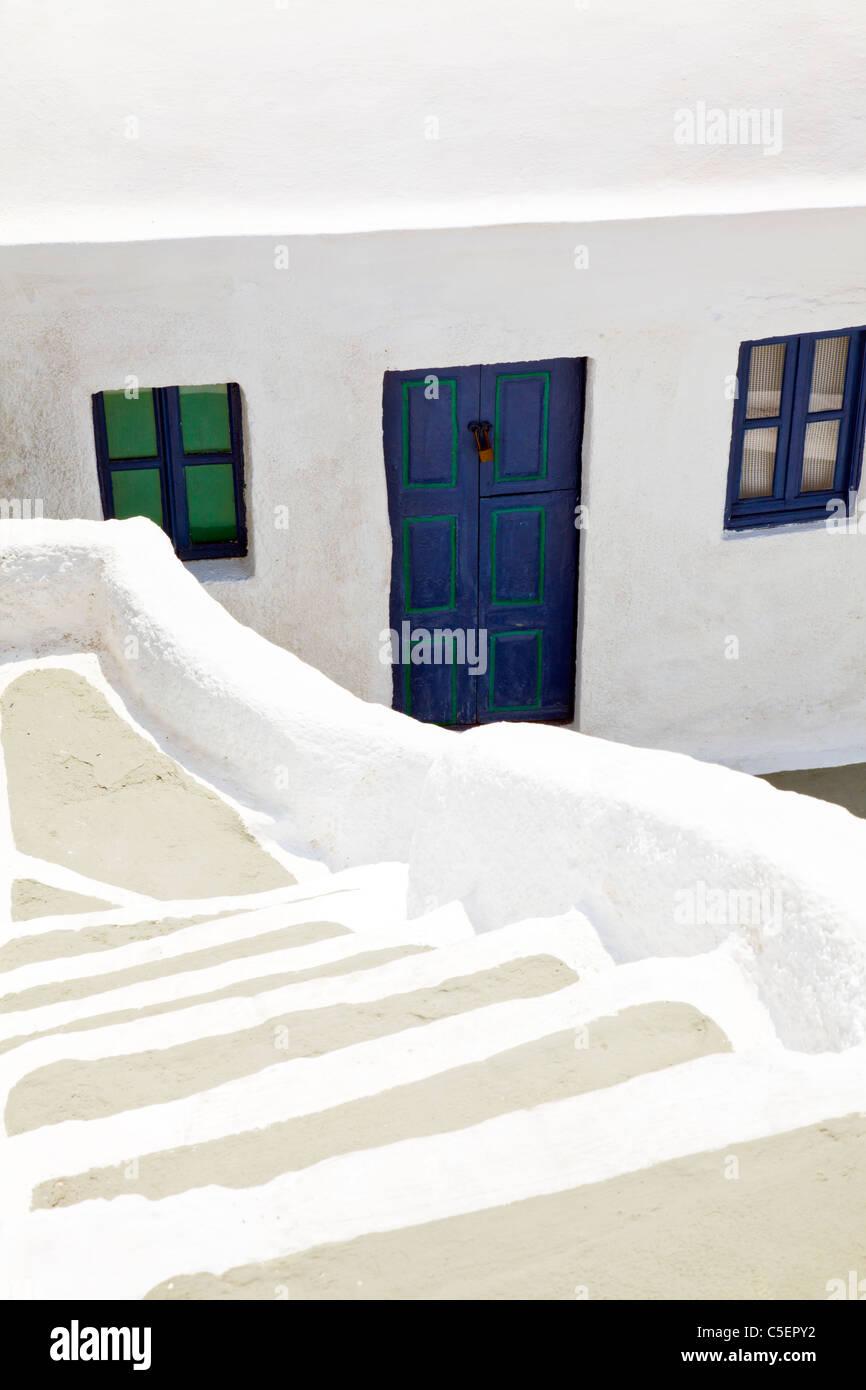Oia - Santorini, isola greca, la Grecia, l'Europa. Iconico edificio dipinto di bianco con porte blu & finestra Immagini Stock