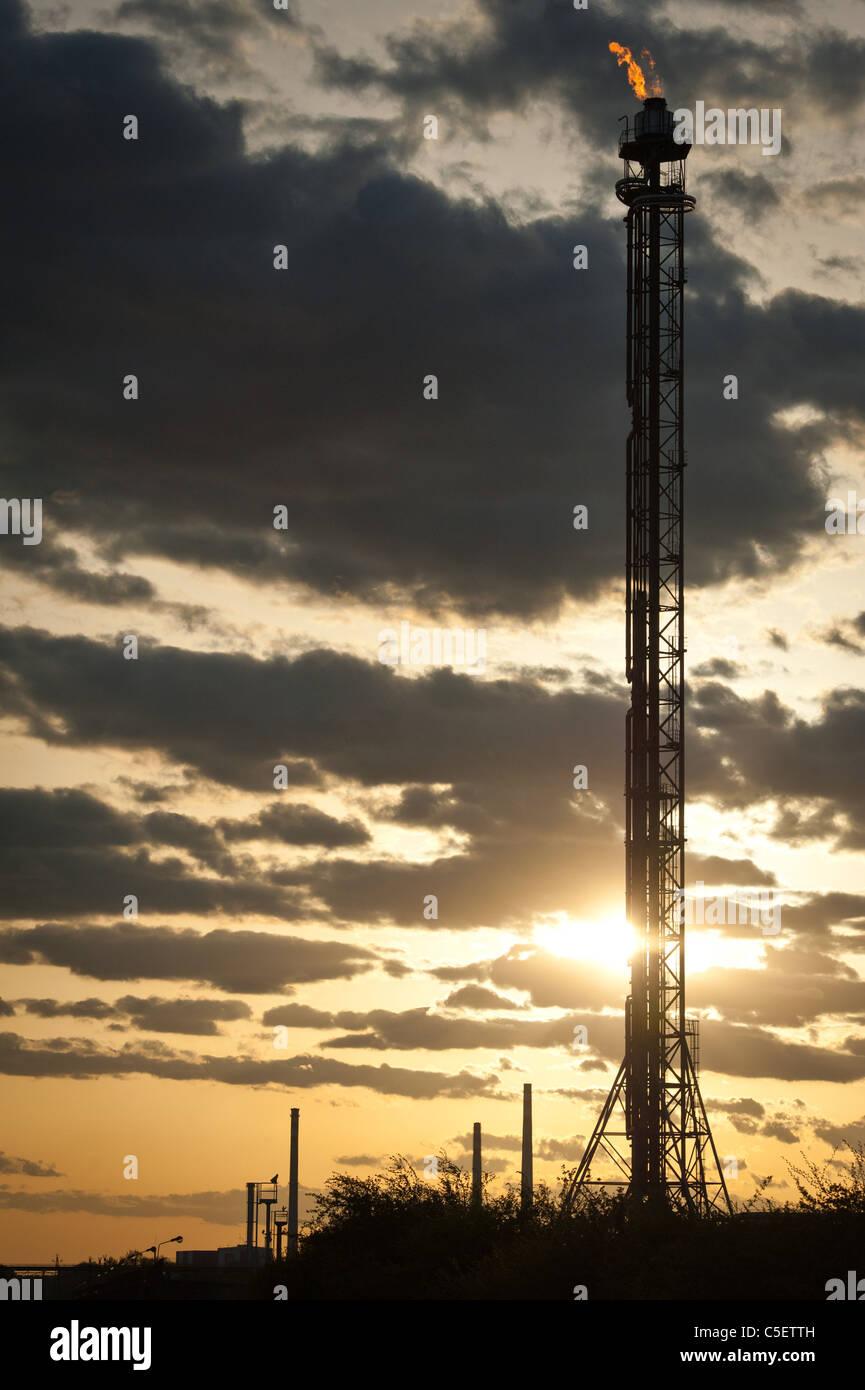 Silhouette di raffineria di petrolio torre al tramonto Immagini Stock