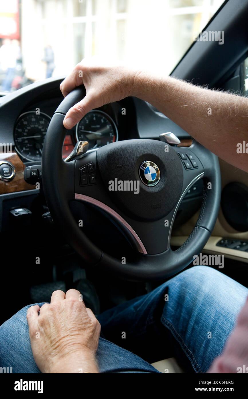 Coppia Mans le mani sul volante di sterzo su BMW Immagini Stock