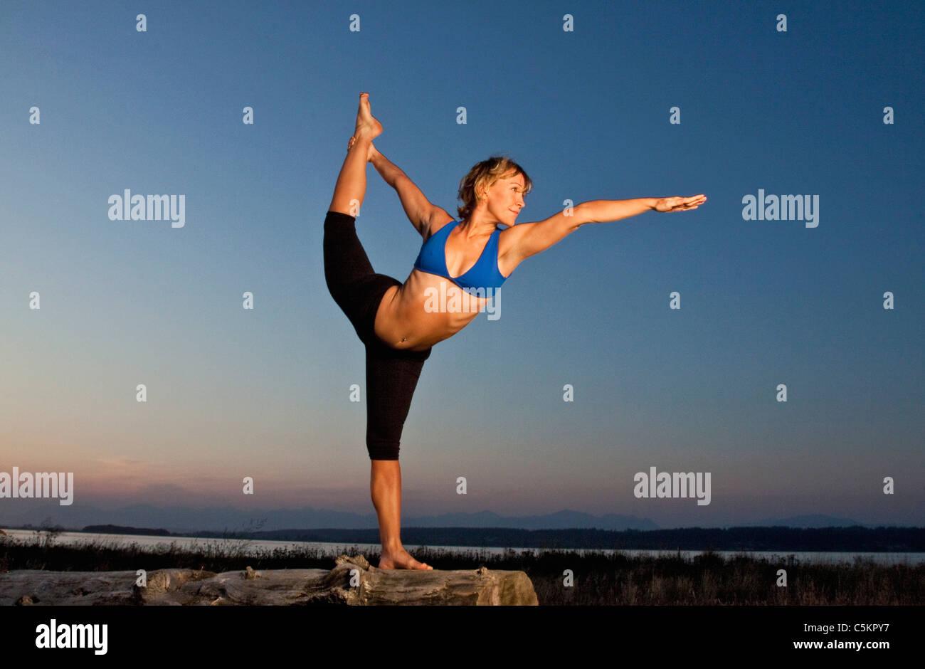 Lo Yoga posa al tramonto, spiaggia a mezzaluna, South Surrey, BC, Canada Foto Stock