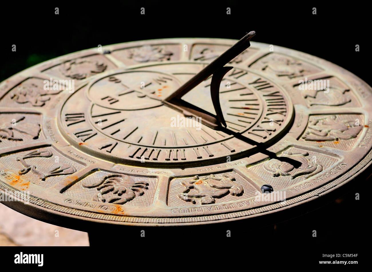 Orologio solare con segni zodiacali e figure che circonda il numero romano volte. Immagini Stock