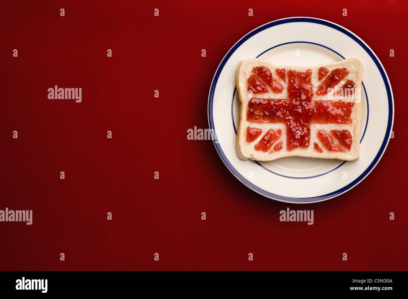 Una fetta di pane con un union jack flag di confettura di fragole Immagini Stock