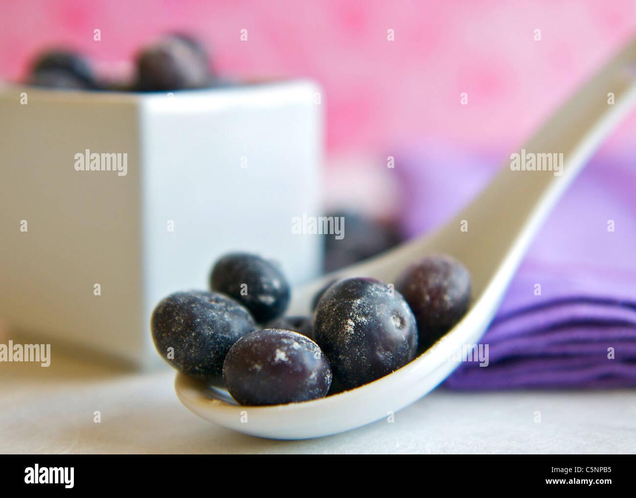 I mirtilli su un cucchiaino di colore bianco Immagini Stock