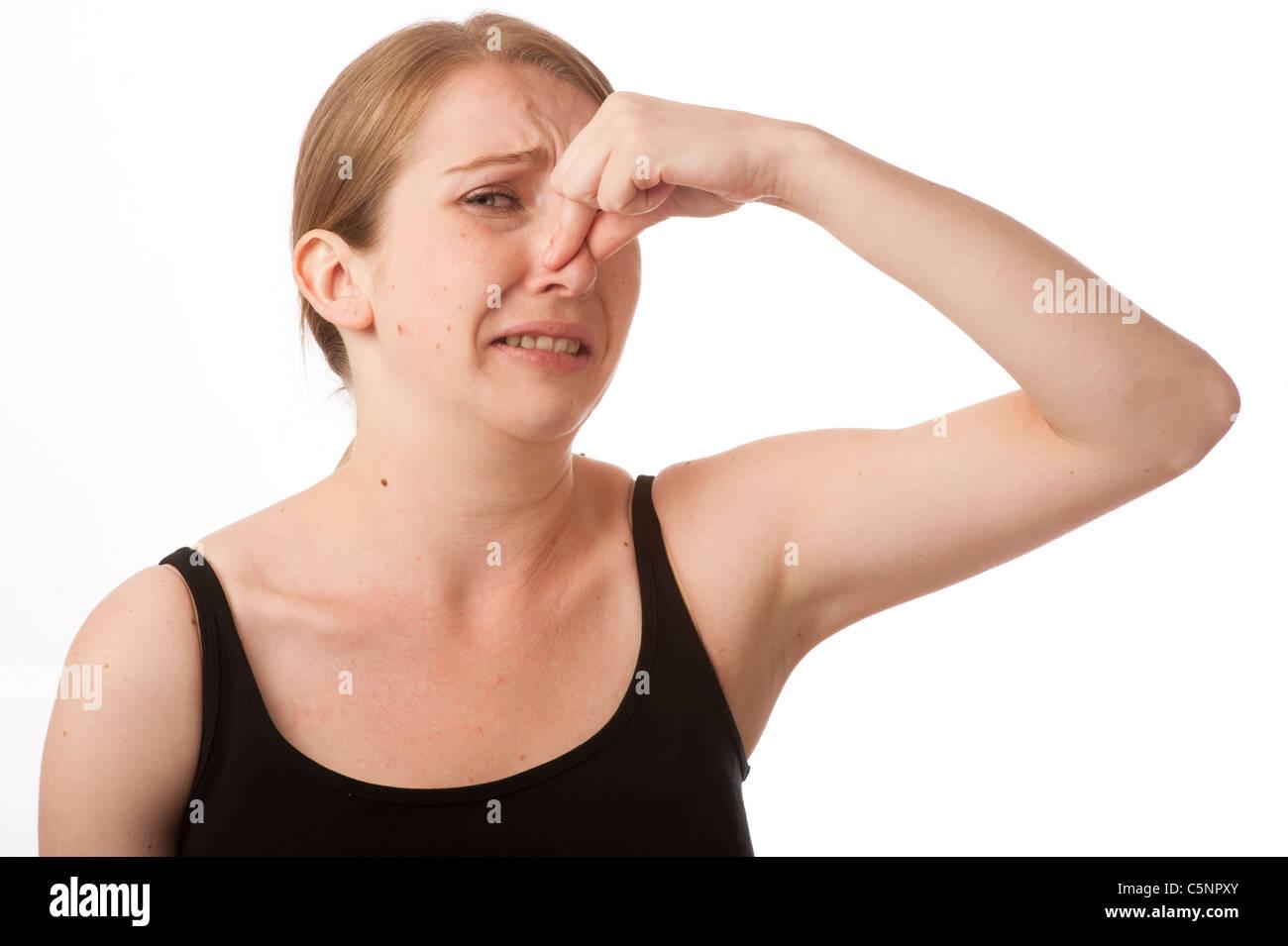 Una giovane donna caucasica mentre tiene il suo naso per evitare un cattivo cattivo odore puzzolente pong Immagini Stock