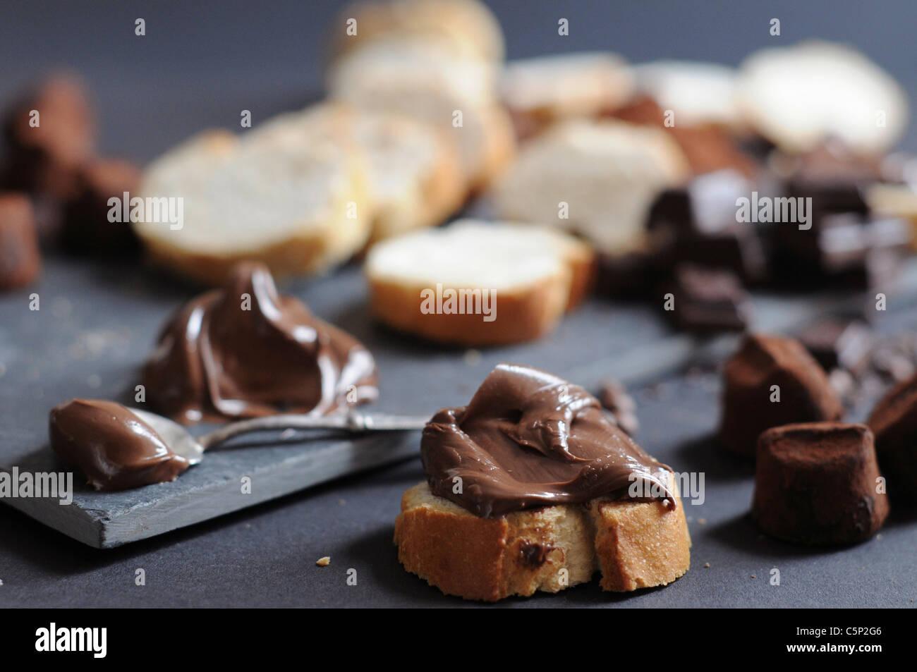 Fette di baguette con crema di cioccolato, pezzetti di cioccolato e tartufi, polvere cokoa Immagini Stock