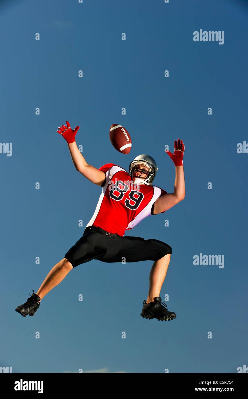 Giocatore di football americano dei salti per effettuare la cattura. Immagini Stock