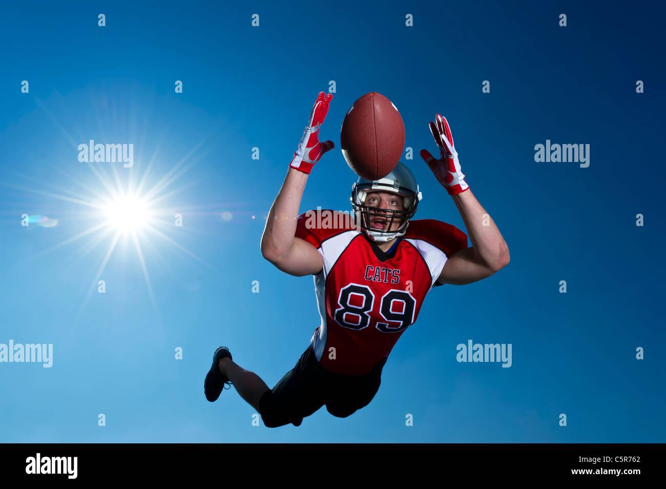 Giocatore di Football Americano volare attraverso l'aria per effettuare la cattura. Immagini Stock