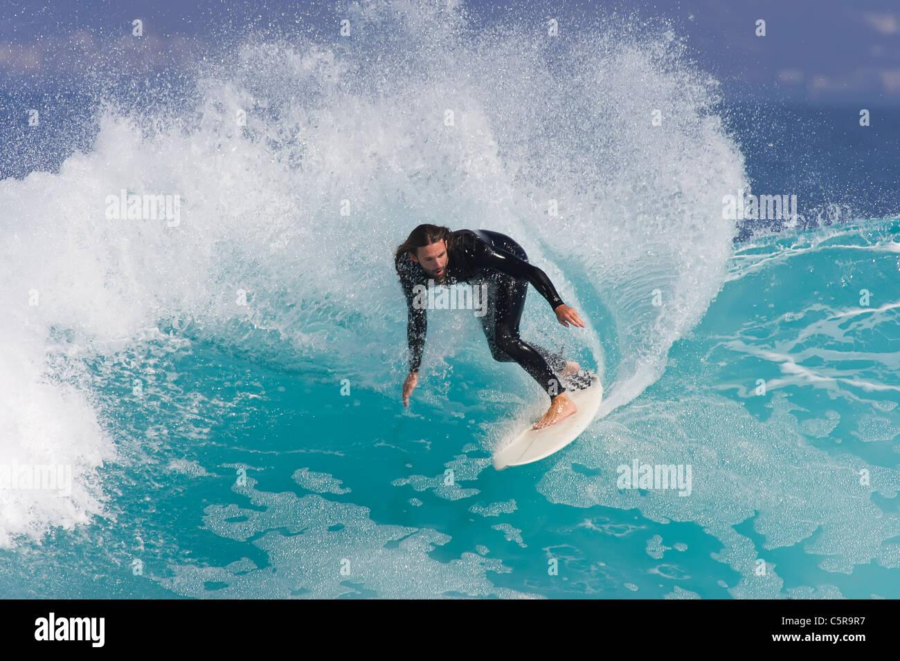 Surfer passeggiate lungo blu azzurro onda. Immagini Stock
