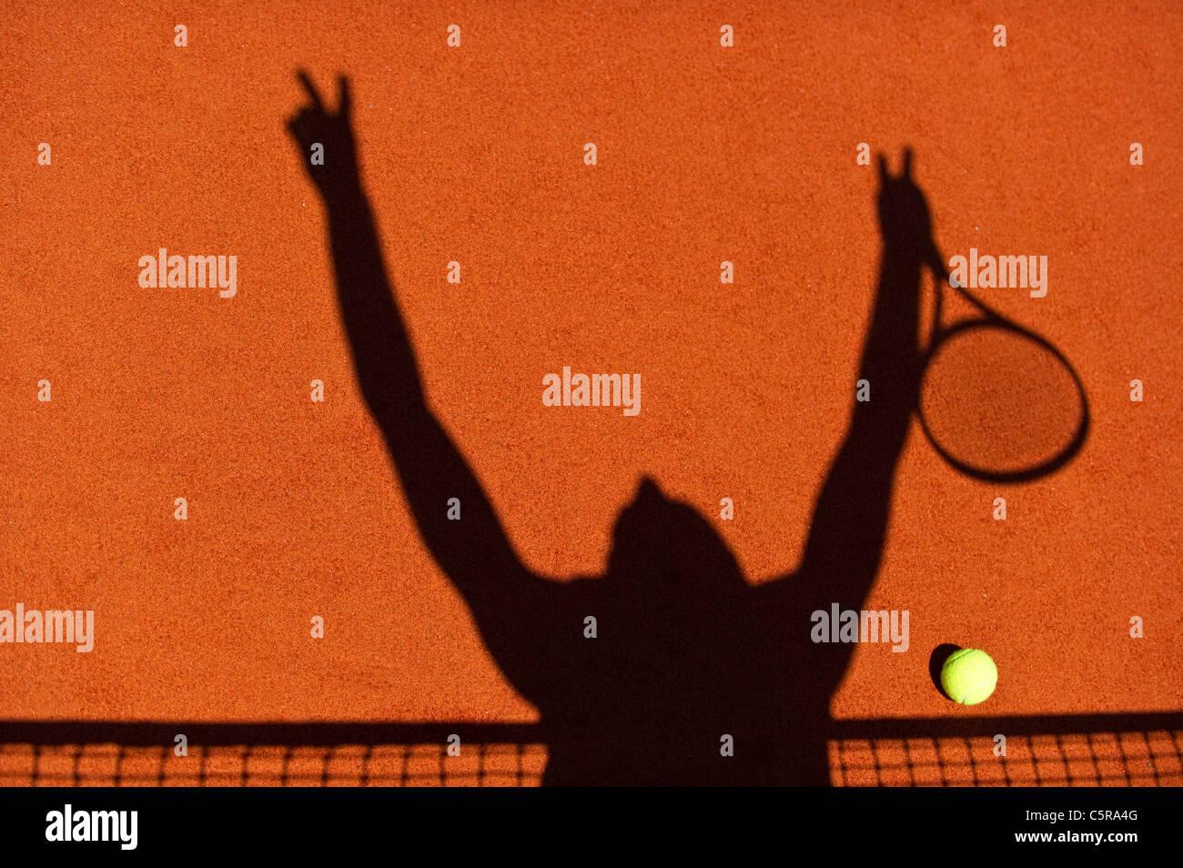 La silhouette di un giocatore di tennis celebrando al netto. Immagini Stock