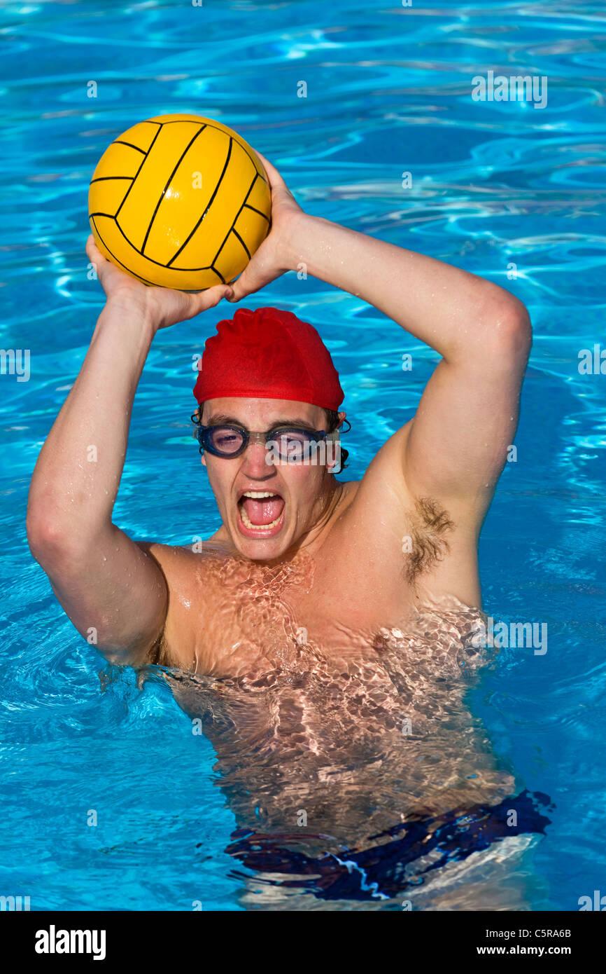 Pallanuoto giocatore le catture a sfera e grida al compagno di squadra. Immagini Stock