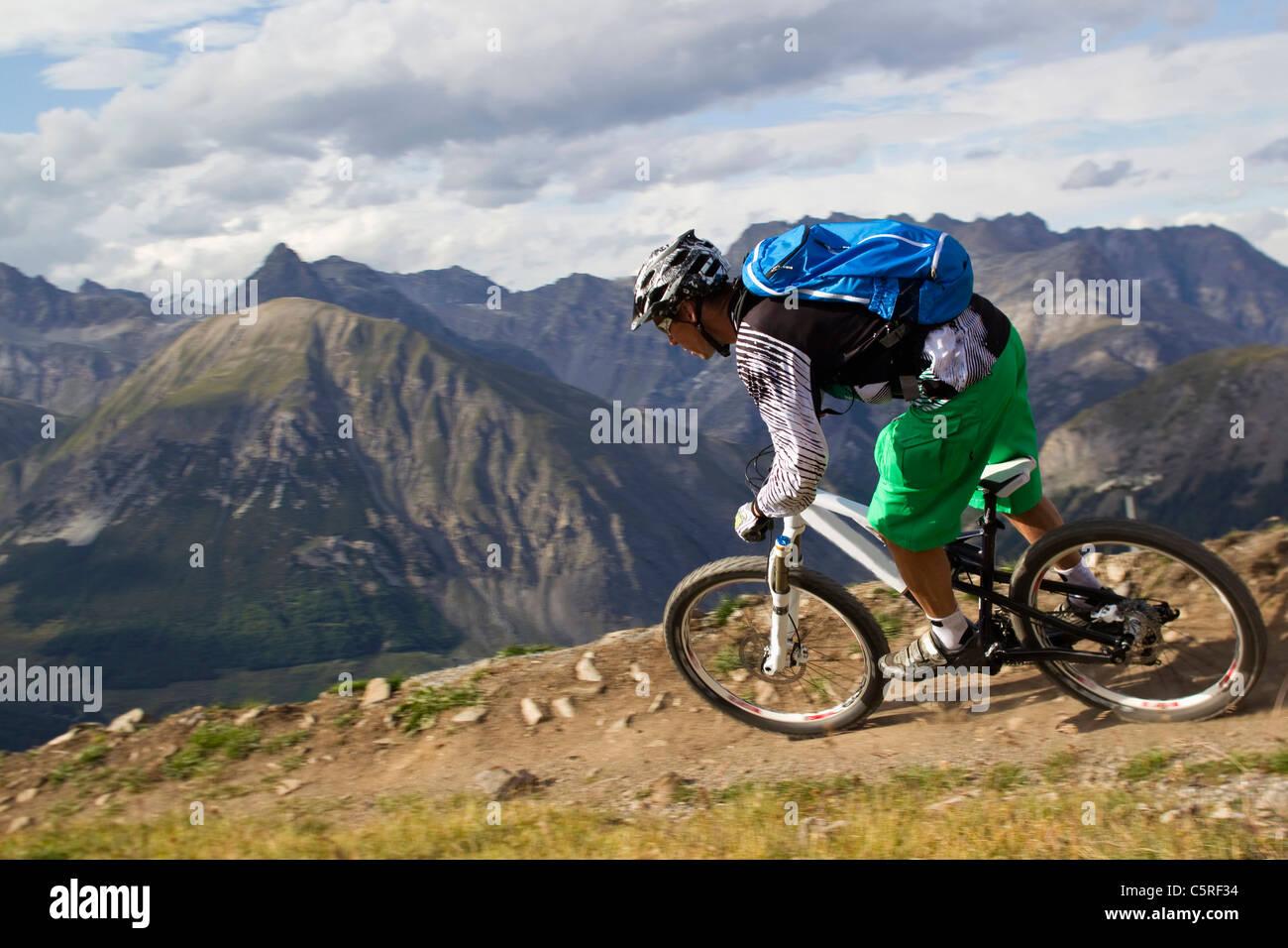 L'Italia, Livigno, vista dell'uomo equitazione mountain bike downhill Immagini Stock