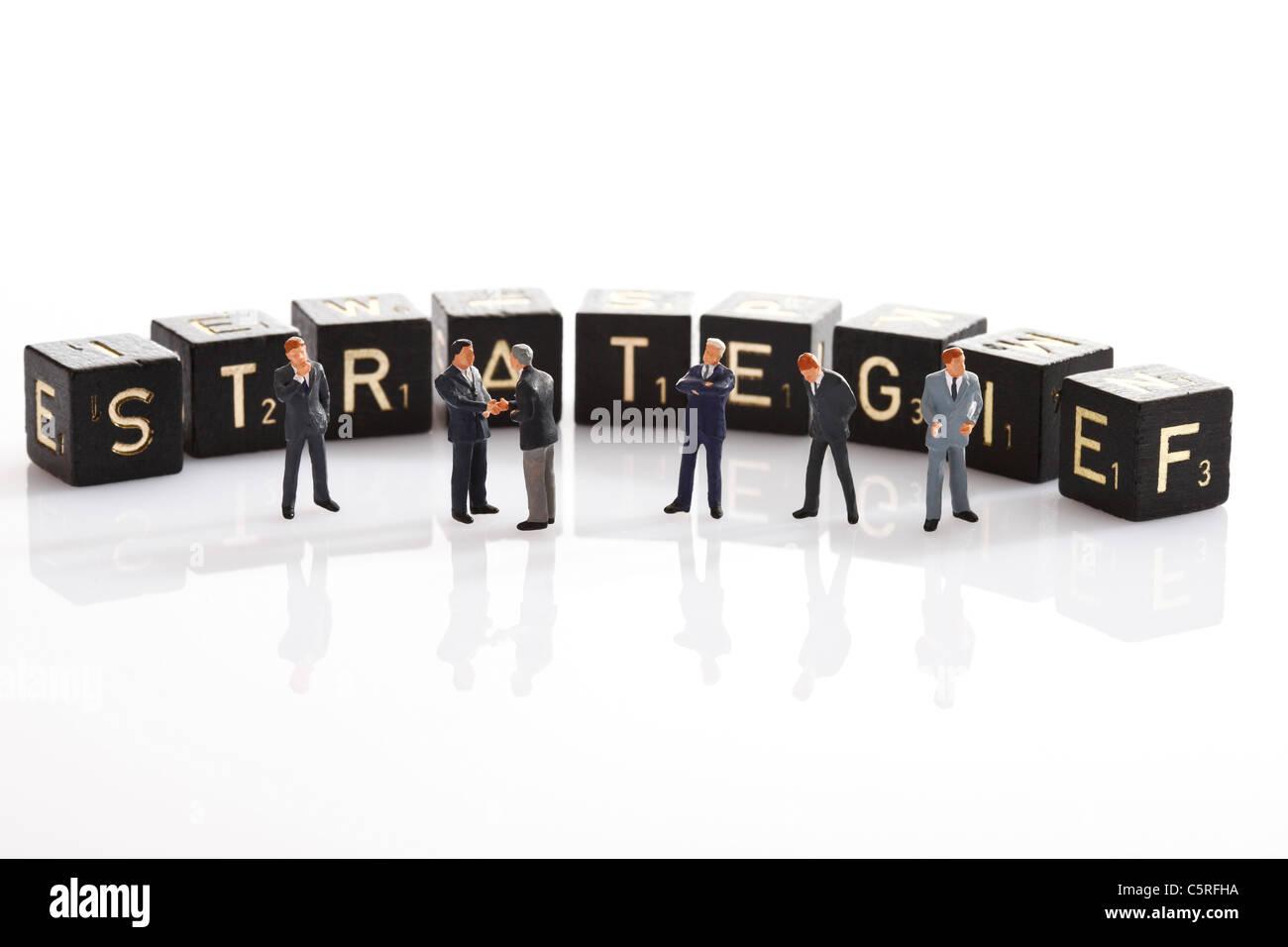 Scrabble le piastrelle che formano la parola singola strategia, in primo piano gli uomini d' affari figurine Immagini Stock