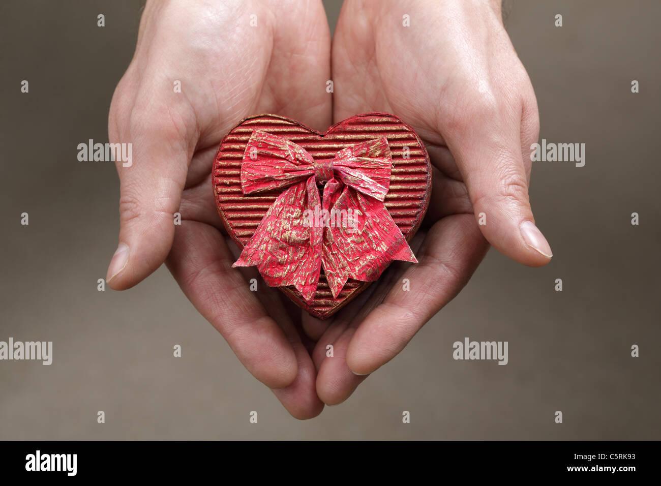 Tenendo un cuore scatola sagomata Immagini Stock