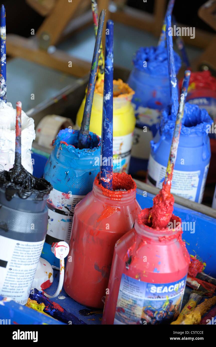 Disordinato vernice acrilica pentole in una camera d'arte impostazione Immagini Stock
