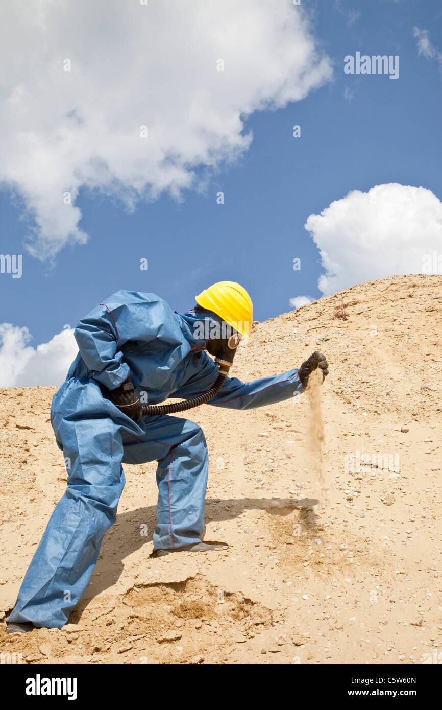 In Germania, in Baviera, uomo in abbigliamento protettivo spargimento sabbia sulla duna di sabbia Immagini Stock