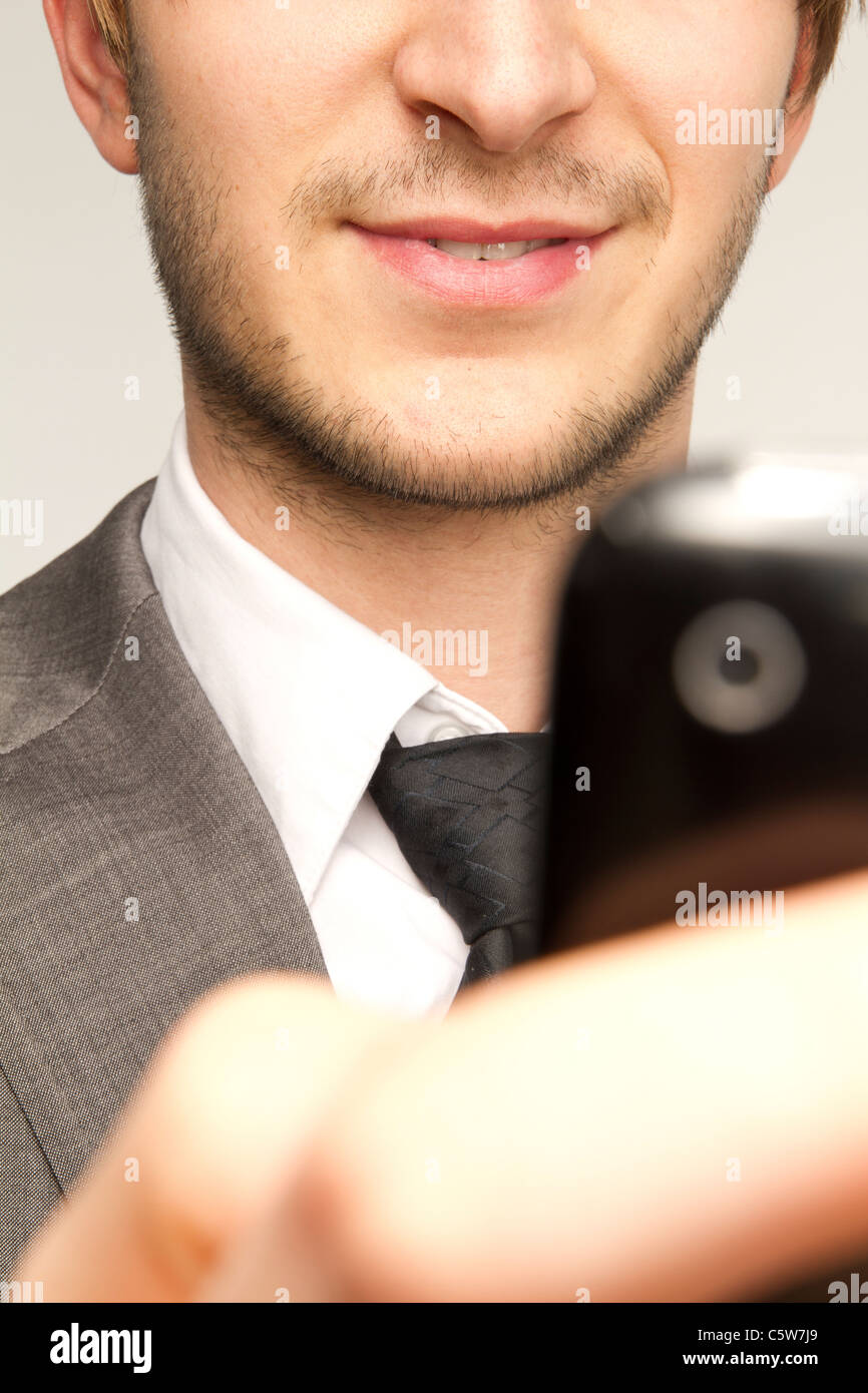 Imprenditore tenendo il telefono cellulare contro uno sfondo bianco, sorridente, close up Immagini Stock