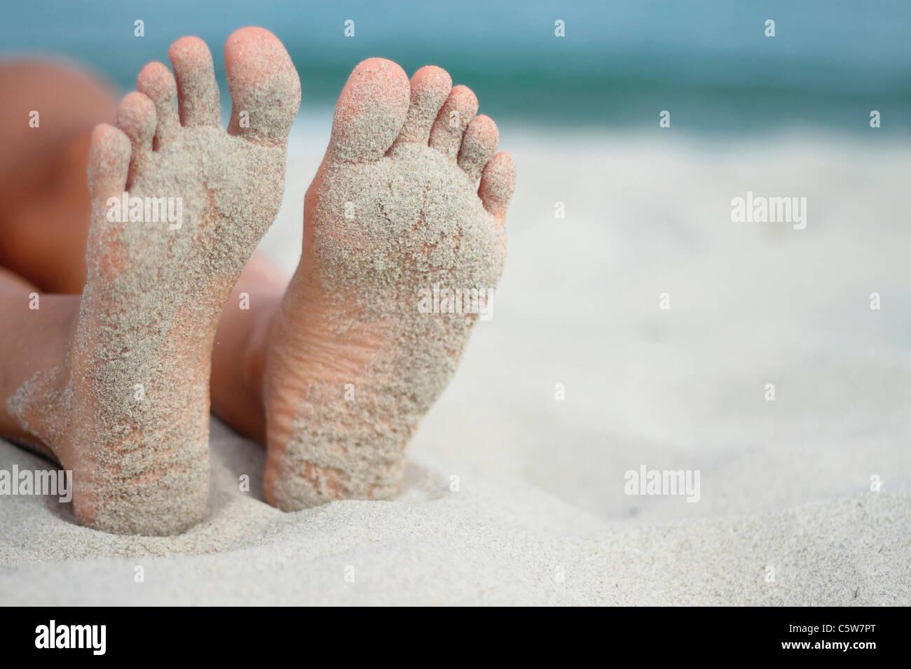 L'Italia, Sardegna, persona sdraiata sulla spiaggia sabbiosa di piedi Immagini Stock
