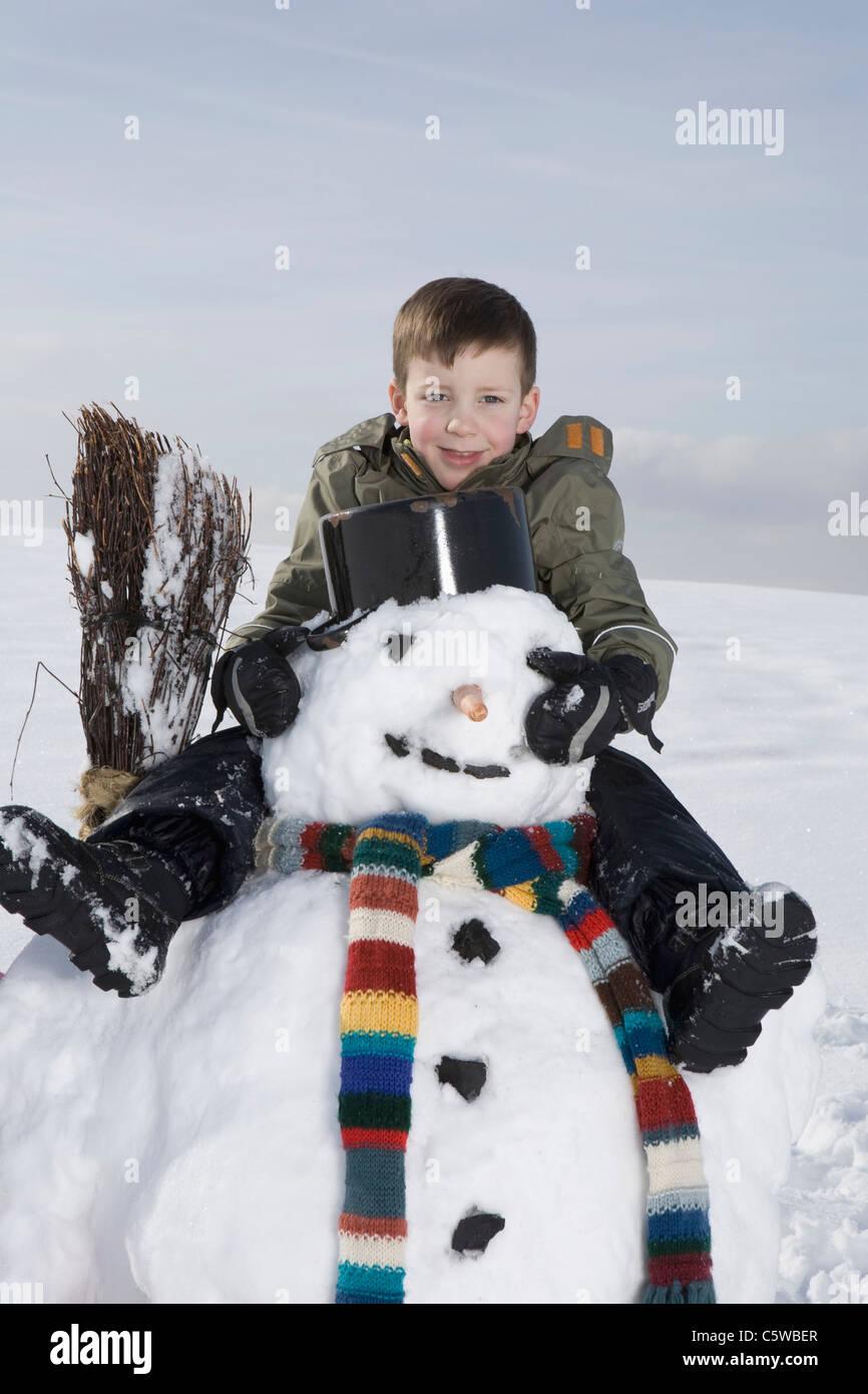 In Germania, in Baviera, Monaco di Baviera, ragazzo (8-9) seduto sul pupazzo di neve, ritratto Immagini Stock