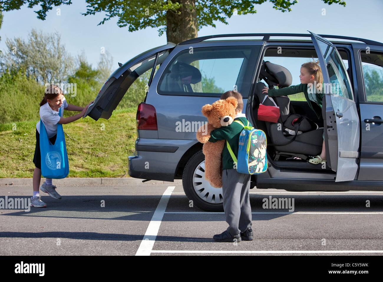 Tre giovani di età primaria dei bambini sul loro modo di scuola in un veicolo per il trasporto di persone Immagini Stock