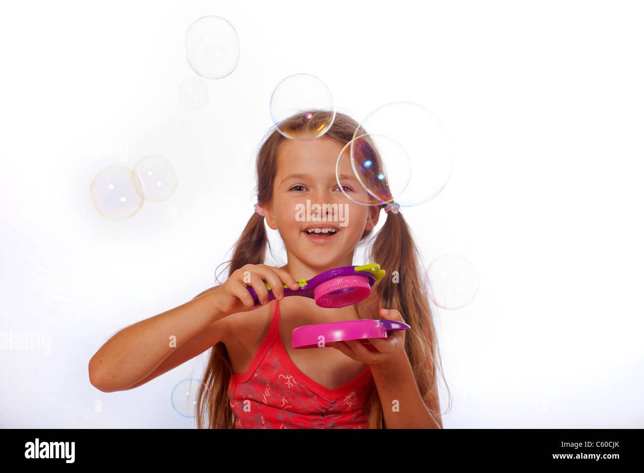 8 anno vecchia ragazza a giocare con le bolle di sapone Foto Stock