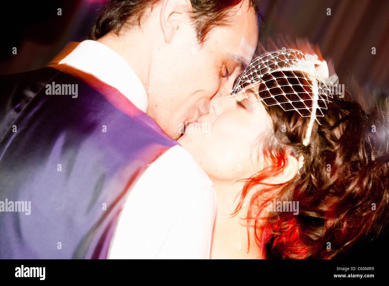 Sposa giovane kissing presso la reception Immagini Stock