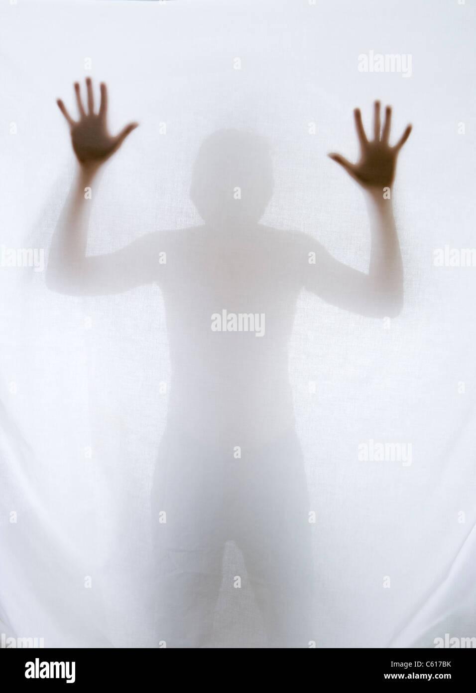 Silhouette di uomo dietro il foglio. Immagini Stock