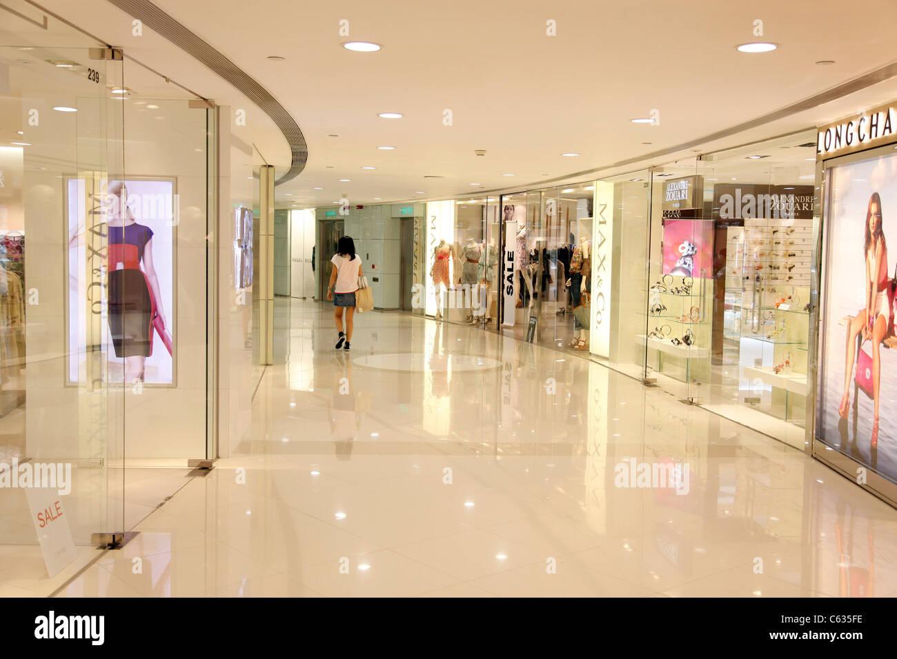 Lungo Il Corridoio In Inglese : Donna che cammina nella distanza lungo un corridoio in un centro