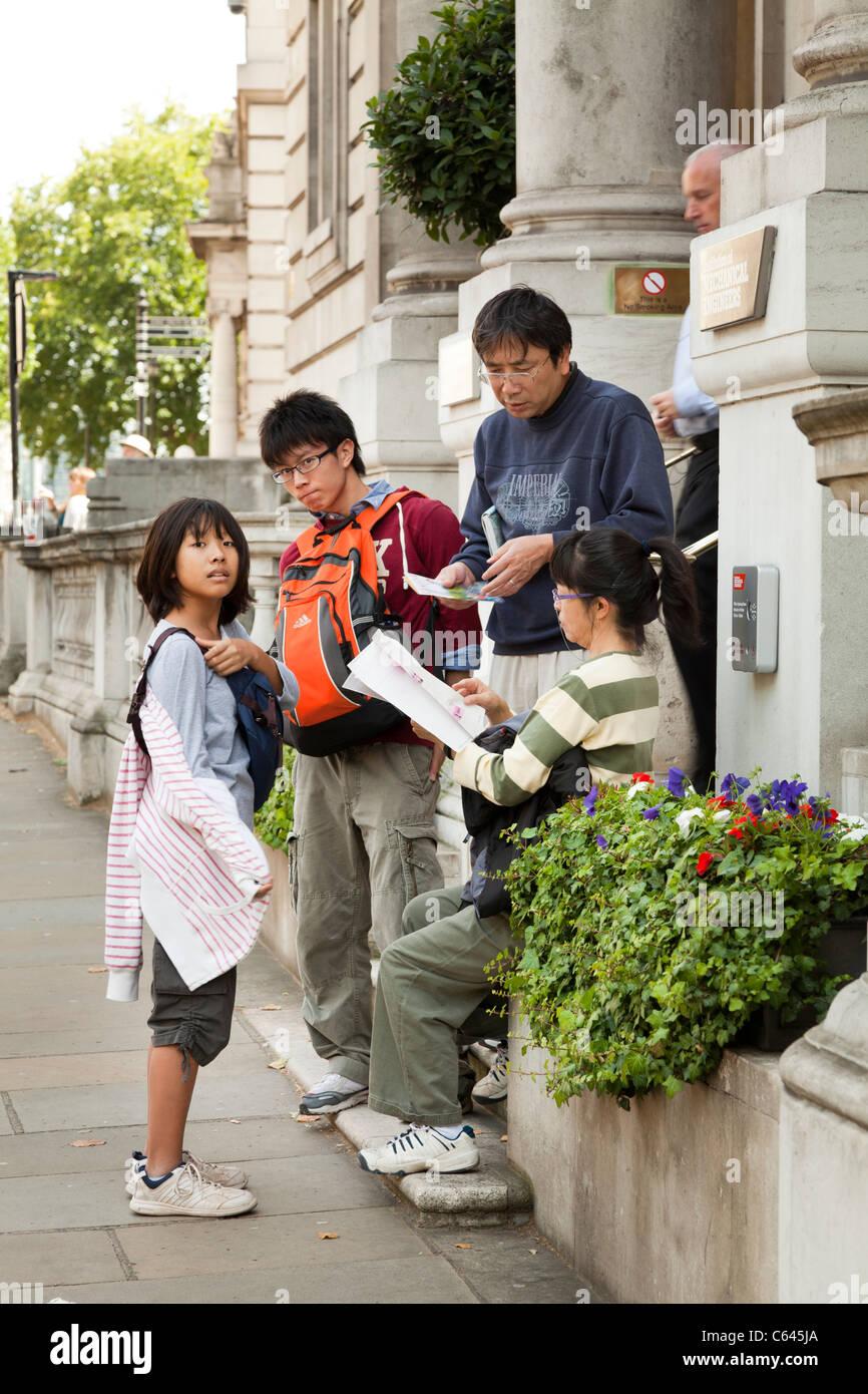Una famiglia di turisti asiatici a Londra consulenza libri guida e mappe Immagini Stock