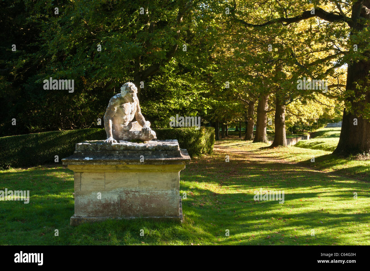 Scheemaker della statua del morente Gladiator si siede accanto a un viale di maturi alberi di quercia a Rousham Immagini Stock